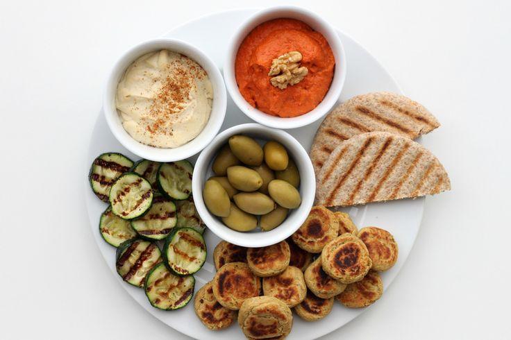 Leckere Rezepte für die perfekte Mezze - Platte: cremiger Hummus, Muhammara, hausgemachte Falafel, Gemüse, Pita und frische Oliven.