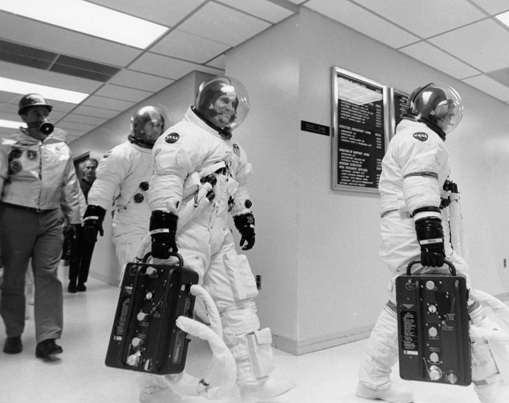 Apollo 16 John Young (right), Ken Mattingly, and Charlie Duke leave the suit-up room, probably headed for the elevator and certainly headed for the transfer van that will take them to the pad for the Countdown Demonstration Test.