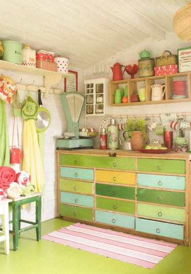 Colourful pink and green shed full of pots, flasks and nic nacs