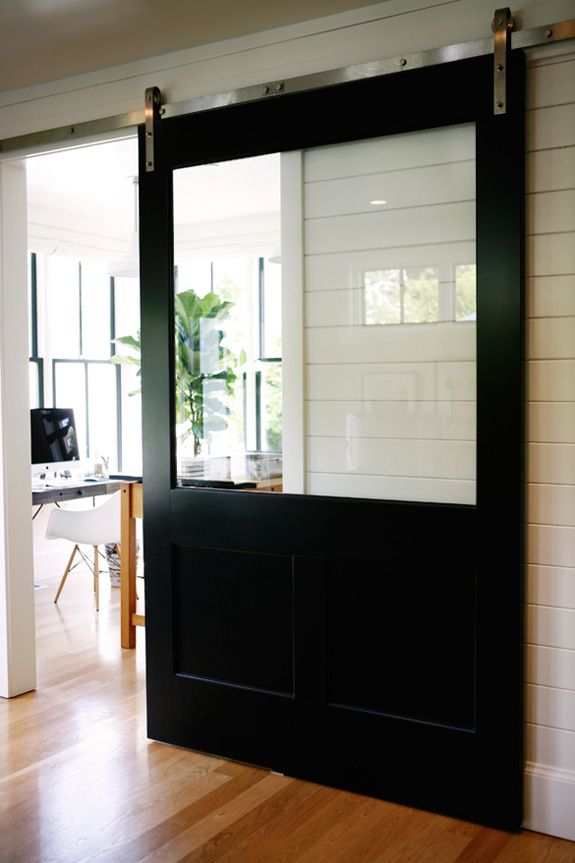 love the large glass panel for light to travel through fresh take on sliding barn doors in a modern washington state farmhouse with interior design by