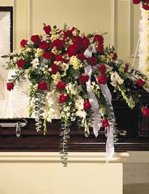 This bountiful casket saddle measures 15''x10.5'' and makes a stately and regal remembrance piece. Red and white blooms of Roses, Snapdragons, white Gladioli, red Carnations, cream Stock, white Monte Casino, soft blue Eucalyptus,...