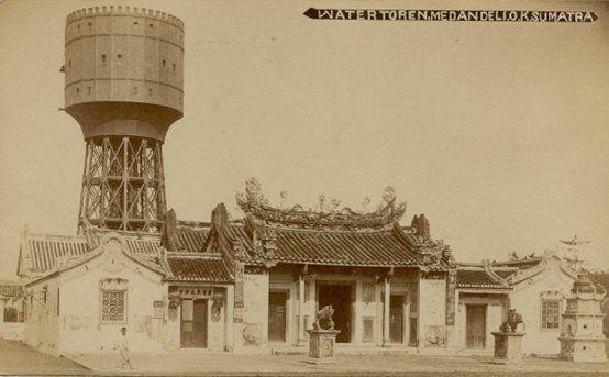 Chineese tempel met achtergrond van de watertoren in Deli, Medan 1879-1881.