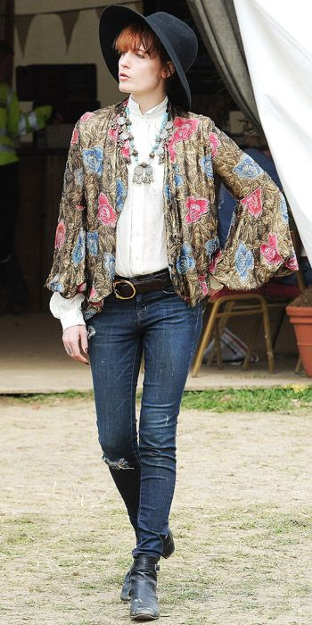 Florence Welch arrived at the Glastonbury Festival in a floral silk jacket over a white blouse paired with jeans and a black hat.
