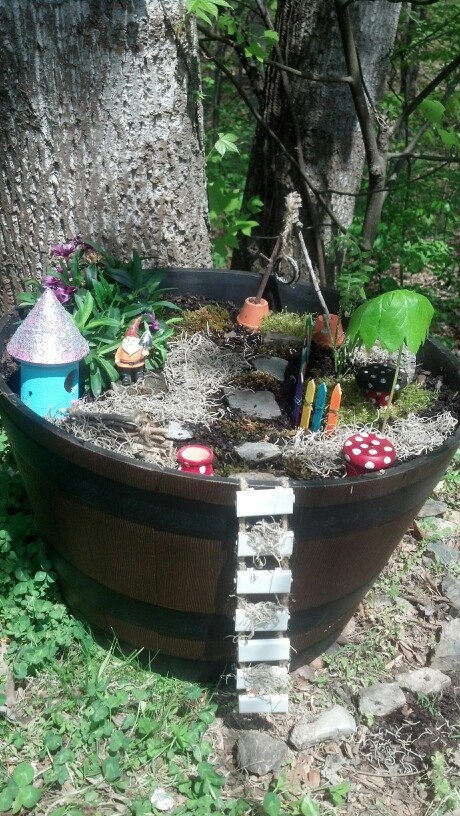 Fairy/Gnome garden. Barrel from Lowes along with flowering plant. Other plants from my woods and yard. Made fence out of popsicle sticks. Made bench, tire swing. Painted wood house and wood spools for mushrooms. Ladder made from left over tile and twine. Planning on adding a door on tree and another ladder going up to the door. Work in progress-Love!