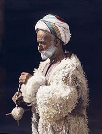 A man from Ramallah spinning wool. Hand-tinted photograph from 1919, restored.