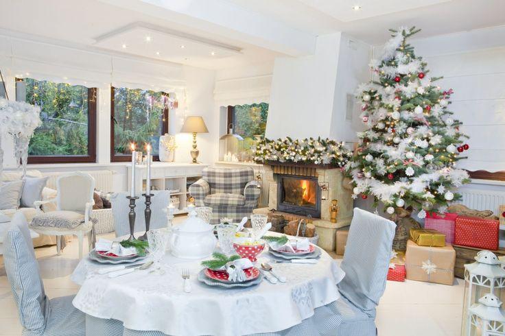 Subtelna aranżacja salonu w bieli zachwyca pięknymi dekoracjami na Boże Narodzenie. Wysoka choinka, girlanda na kominku i dziesiątki migocących lampek tworzą w salonie magiczną atmosferę świąt.