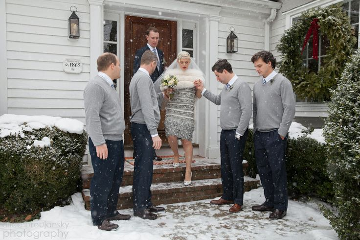Snow starts to fall on groomsmen in gray sweaters and a winter bride in a short, gray Chanel wedding dress with white fur and white Chanel heels. A sophisticated take on a snowy, New England wedding.