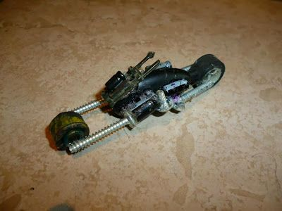 Para hacer la base de la moto, usé parte de un audífono de celular.  Las llantas son de juguetes descartados y están unidas a la base por piezas de tarjetas de memoria de computador, conectadas a tornillos.   Hecha en 2012