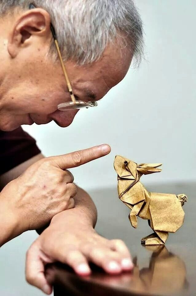 Origami rabbit looking into man's eyes. CUTE!!!
