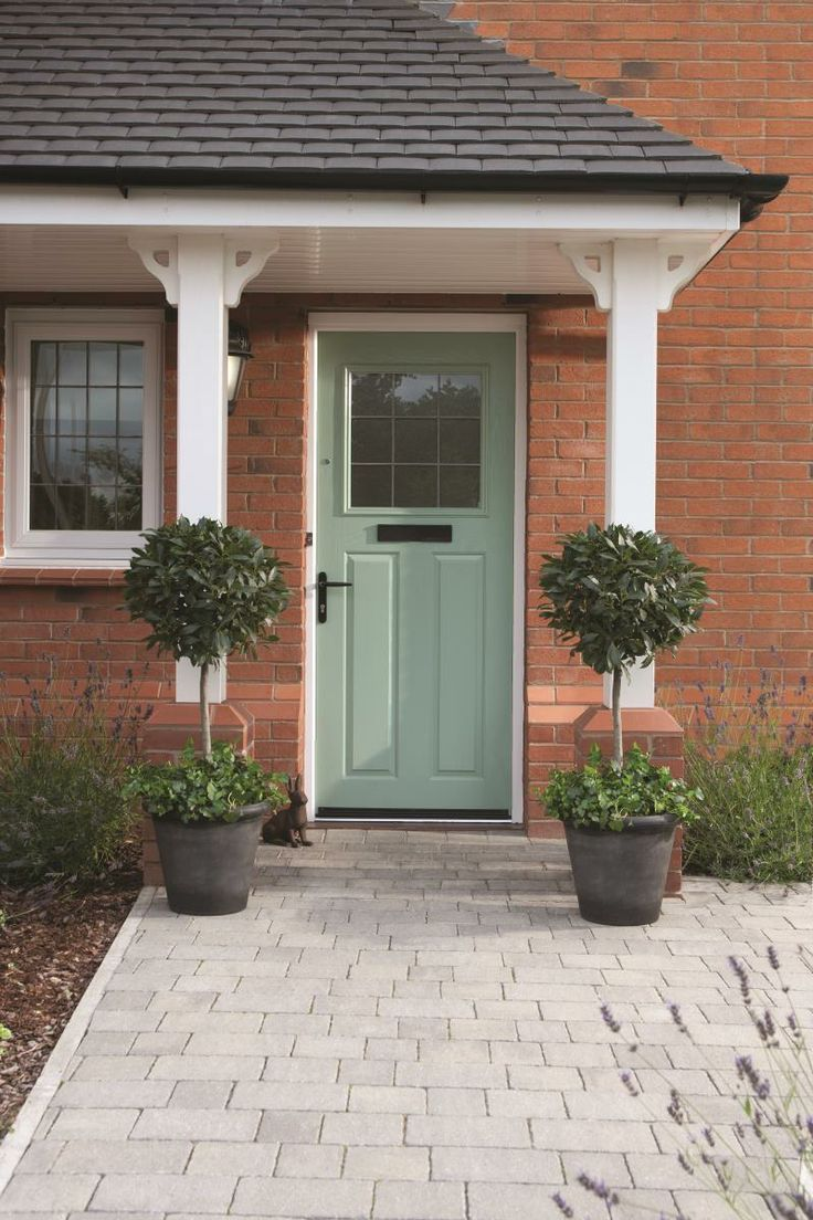 A charming front door in a vintage shade of green. The trees either side of the doorway echo the symetry of the porch uprights. The paved driveway in grey looks smart, too.