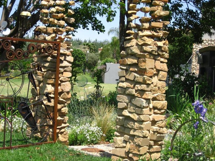 Stone pillars disappearing into the sky, with fun custom made rusted steel gate