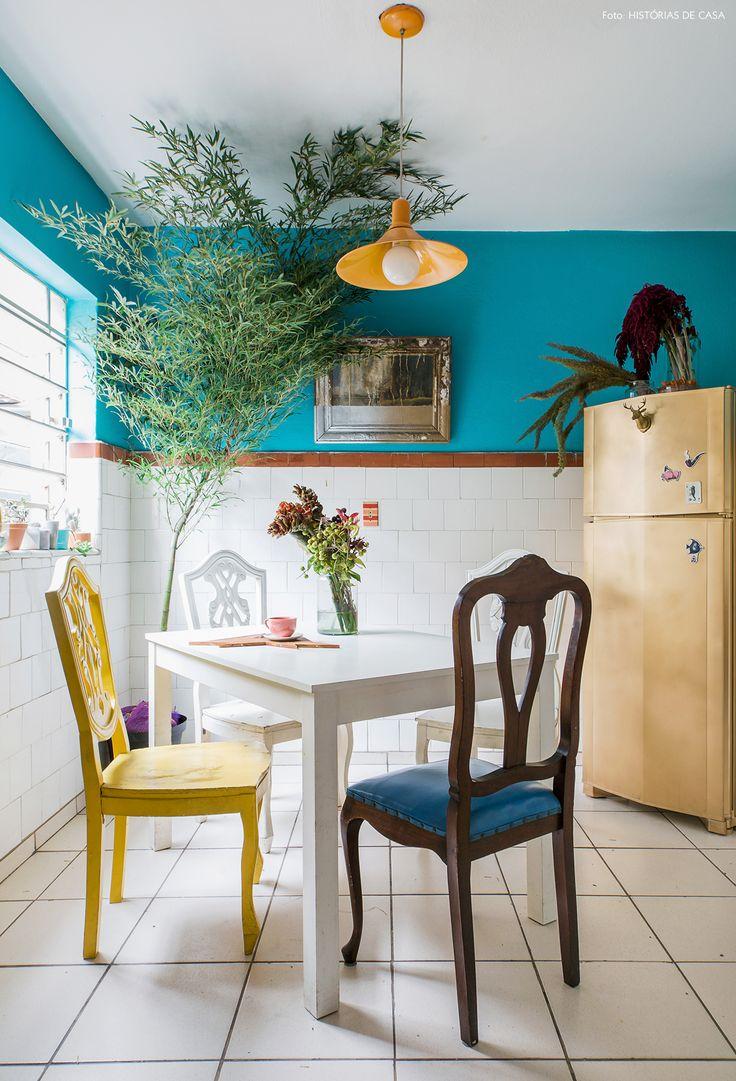 Cozinha de casa compartilhada tem meia parede pintada de azul, cadeiras antigas e geladeira renovada com pintura dourada.