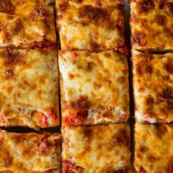 A fabulous recipe for thick-crust Sicilian pizza, complete with homemade sauce and tons of cheese... Cut into squares, of course!