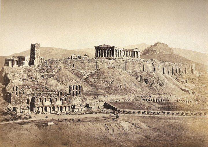 Η αρχική φωτογραφία τραβήχτηκε το 1854 από τον Ρόμπερτσον Τζέιμς. Απεικονίζει τα Προπύλαια της Ακρόπολης και μερικούς ανθρώπους που στέκονται κοντά στην είσοδο. Ανάμεσα τους ξεχωρίζουν δύο άντρες π…