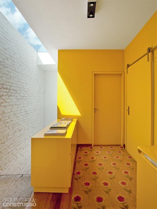 A luz natural entra pela claraboia e é refetida pelo branco dos tijolinhos que revestem a parede de blocos cerâmicos. Cortados na obra, fcar...
