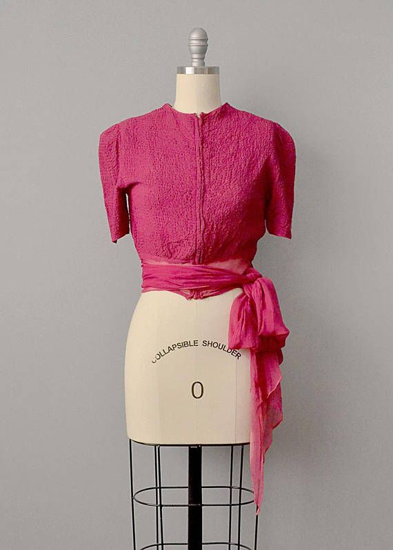 This gorgeous blouse from the 1930's is made from raspberry colored silk chiffon which has been elaborately textured by topstitching in a checkered pattern — creating a puckered, seersucker-like texture. Has a high, rounded neckline, with a metal zipper up the front. The puffed
