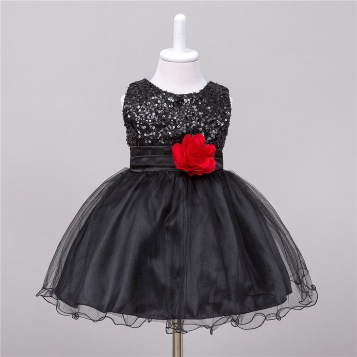 Feestelijk zwart jurkje met pailletjes op het bovenstuk, rode bloemversiering op het voorpand en aanknooplint op het achterpand. Het rokje bestaat uit twee lagen organza, een polyester onderlaag en daaronder een binnenrokje. Kuitlengte.   Model: Louise Baby