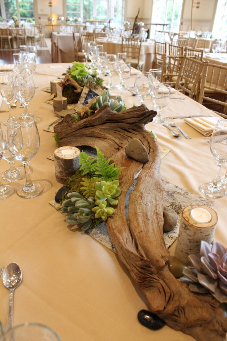 Tablescape featuring driftwood, ferns, succulents, birch candles, and other organic accents