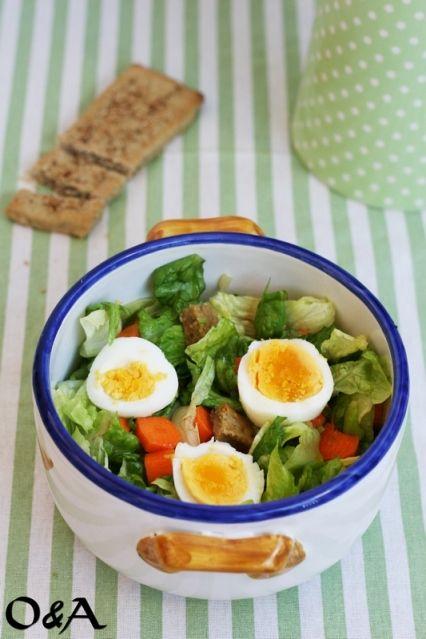 La Caesar salad con uovo sodo, carote e crostini al sesamo