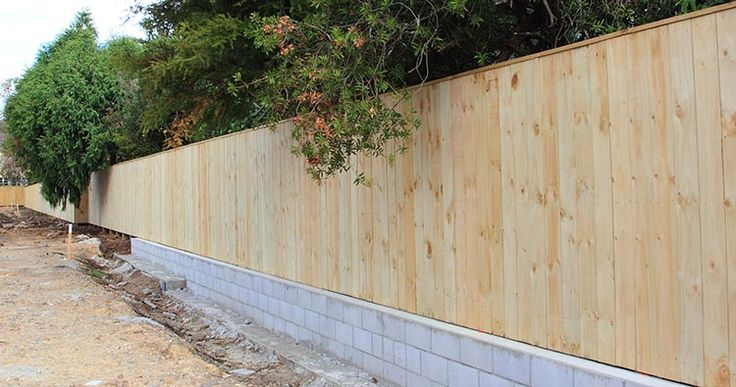 Plain board wooden fence on a brick wall