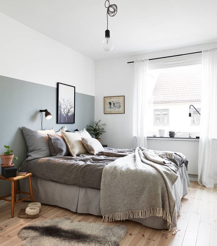 Simple, yet stylish and cozy bedroom. Really like the partially painted wall (love! that color), the single light bulb lamp, the sheep skin on the floor, the blanket randomly laying on the bed and all the light streaming in from the windows. Scandinavian/Nordic apartment in Gothenburg, Sweden.