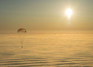 A Szojuz TMA–14M ejtőernyős ereszkedése a Föld sűrű légkörében az arany felhők tengere felett 2015. március 12-én, röviddel napkelte után a kazahsztáni földet érés előtt