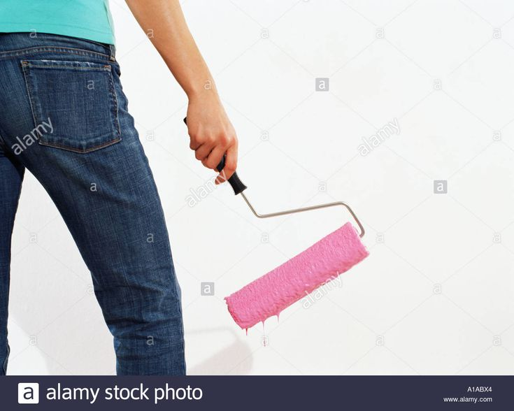 Download this stock image: Woman holding a paint roller - A1ABX4 from Alamy's library of millions of high resolution stock photos, illustrations and vectors.