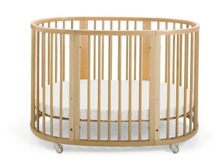 Stokke Sleepi Bed, Natural. Unique oval-shaped convertible crib with a height-adjustable mattress & lockable swivel wheels too.