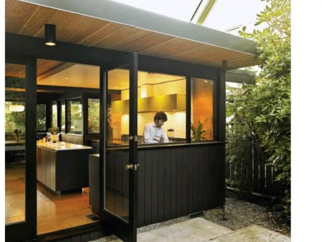 FURTHER INTEGRATING INTERIOR AND EXTERIOR SPACES, A LARGE FULLY GLAZED DOOR  SWINGS OPEN FROM THE