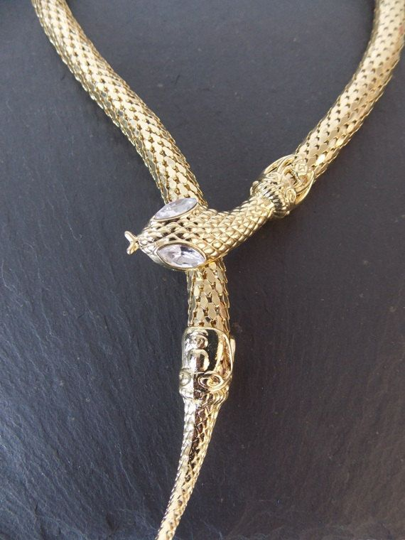 A gold tone vintage style snake necklace from Olivia Divine.  Cleopatra snake wrapover design.  Made from mesh style metal.  Perfect for a glamorous occasion.  See our collection of stylish statement jewellery