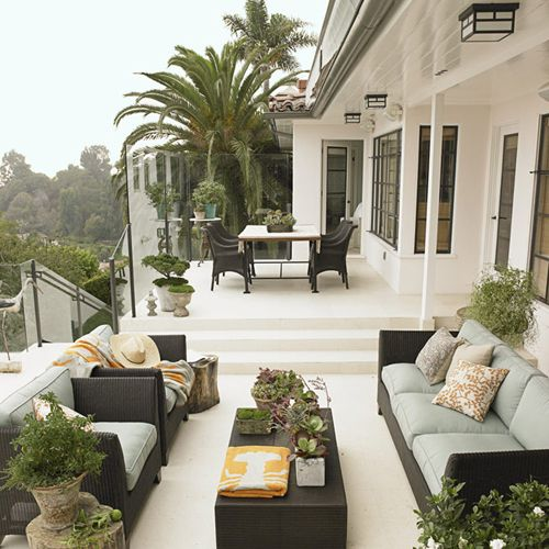 Divided Outdoor patio with living area space and dining area elevated up the steps. Rattan furniture with cushions.