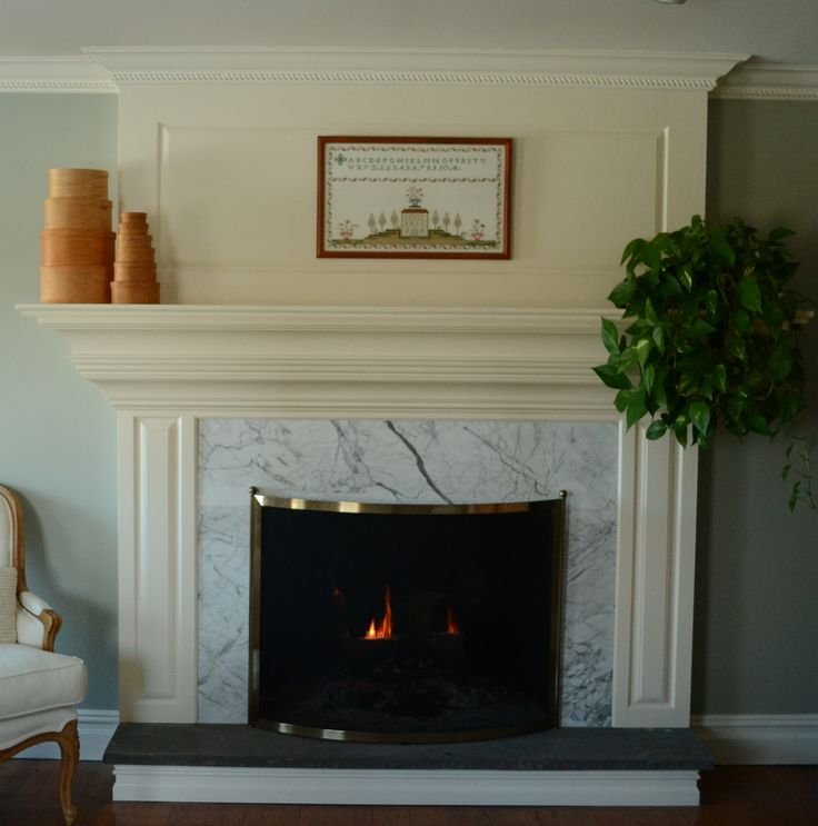 White Fireplace With White Tile Surround And Black Hearth