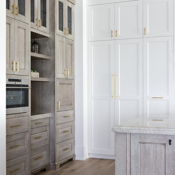 Floor to ceiling white shaker cabinets accented with long brass pulls are fixed adjacent to gray oak shelves mounted under glass front cabinets and between gray cabinets fitted with a microwave drawer.