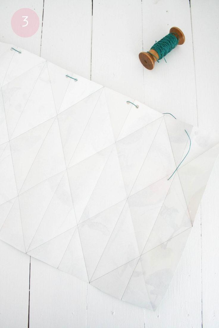 lampe papier origami et enfilage du fil de coton en gros plan
