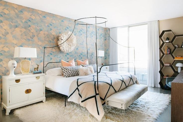 Elegant contemporary bedroom is furnished with a lucite bench placed on a white sheepskin rug in front of an Anthrologie Campaign Bed.