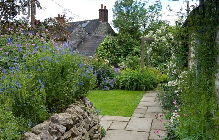 Harpur Garden Images Ltd :: slater78 Dry stone retaining wall and raised bed border Geranium Salvia paving slab stone path lawn border pergola Rosa Rambling Rector Alchemilla mollis Design: David Stevens for Kevin Slater, Creamery Cottage, Parwich, Derbyshire, UK Jerry Harpur Dry, stone, retaining, wall, raised, bed, border, Geranium, Salvia, paving, slab, stone, path, lawn, border, pergola, Rosa, Rambling Rector , Alchemilla, mollis, Creamery Cottage, Parwich, Derbyshire,, UK, Jerry Harpur,