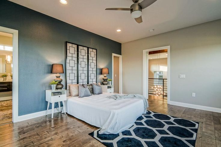 Varying hues of gray on the walls create depth and dimension in this spacious master bedroom. A bold area rug breaks up the beautiful wood floors, and crisp white bedding keeps the space looking clean and fresh.