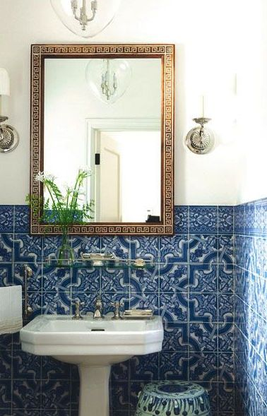 Decorative blue wall tile, Antique mirror, and pretty wall sconces.