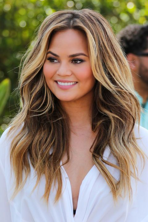 Honey-spun blonde, seen on Chrissy Teigen. This summer, transform your hair (and look) with this or one of 7 other new colors to try—all high shine and beautiful.