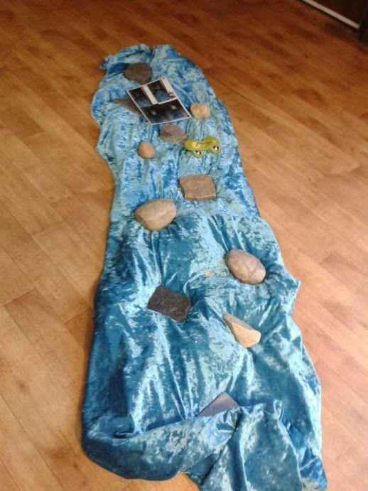 plastic zeil met blauw doek over. Maak een pad met grote en kleine stenen om over te lopen.