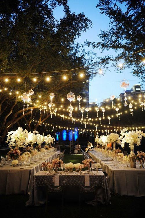 outdoor wedding reception with hanging lights and long table settings