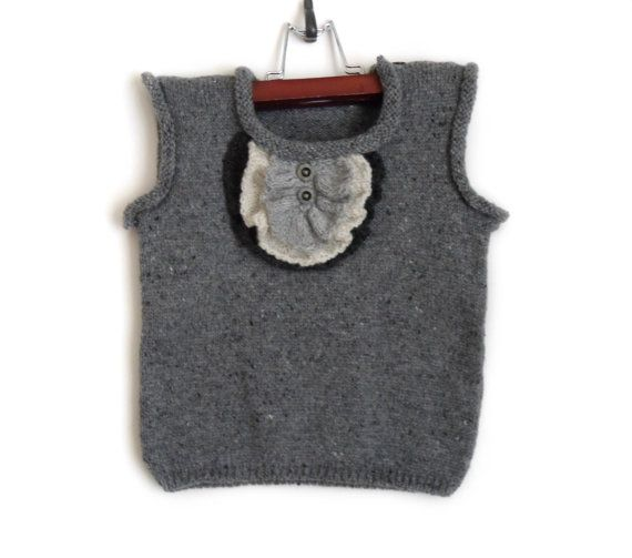 This baby boy vest is knitted from 60% wool, 40% acrylic yarn. Decorated with knitted ruffle and grey buttons. Size: 2T (86 - 92cm)