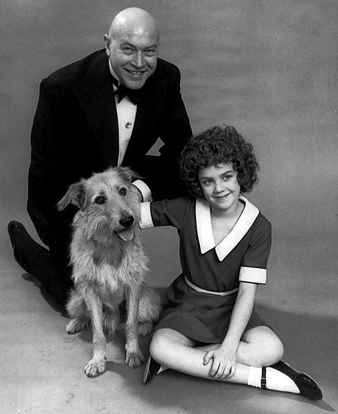 Andrea McArdle as Annie, Reid Shelton as Daddy Warbucks and Sandy from the Broadway musical Annie, 1977, public domain via Wikimedia Commons.