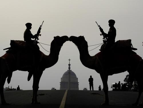 Indian soldiers from the Border Security Forces atop camels stand at attention in front of the Presidential Palace during a ceremony in preparation for the annual Beating Retreat in New Delhi, India
