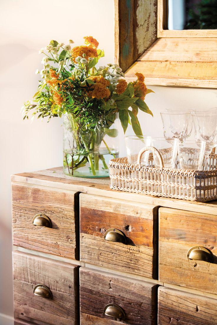 Aparador de madera con bandeja con vasos y copas de cristal y ramo de flores_452178