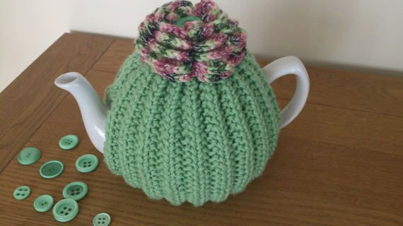 Green hand knitted tea cosy with a crochet flower top  to fit