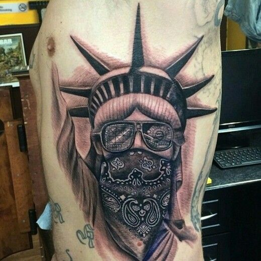Statue of liberty tattoo with coney island in the sunglasses reflections