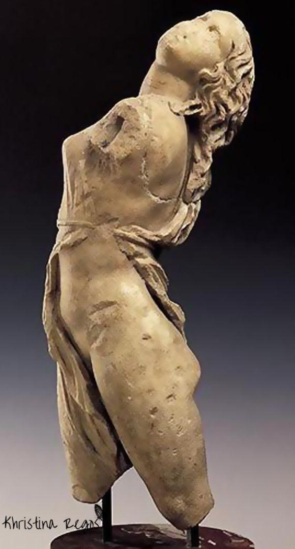 Es una bailarina, y aunque no tiene brazos, por la inclinación de la espalda y la pose de las piernas y la cabeza se ve como el artista intenta reflejar un paso de baile. La textura de la escultura, a pesar de ser una imagen se ve que es áspera y rugosa.