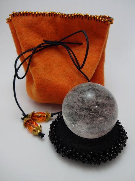 Esfera de Cristal de Quartzo com ótima transparência.  Acompanha linda bolsa de feltro, na cor laranja com interior preto.  Bola de cristal: 3,5 cm de diâmetro e 60g  Bolsa de feltro: 22cm de diâmetro