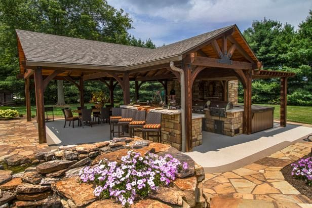 This outdoor entertaining space features an open pavilion with TV, kitchen and fireplace. The nearby pool provides a great place for…